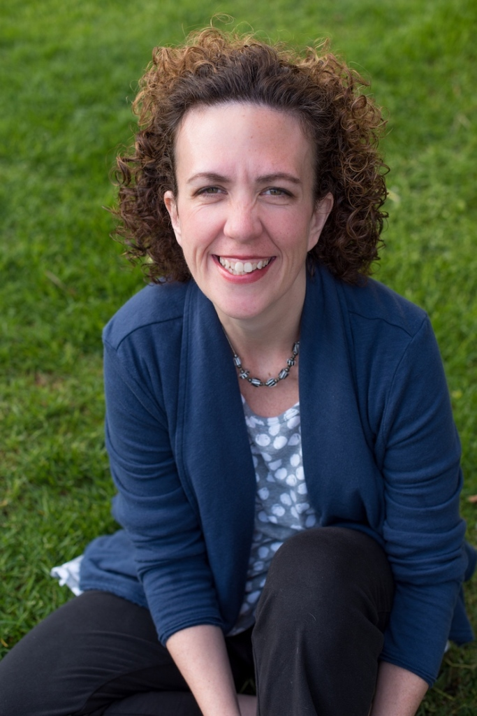Lisa Witzleben, founder of Unclutter Me, sitting on the grass smiling